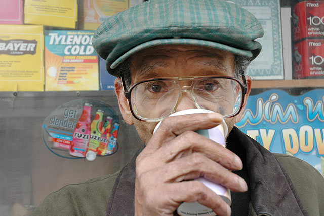 Man with big eye glasses and a green hat drinking coffee